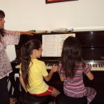 Alunne del corso di pianoforte impegnate in un brano per pianoforte 4 mani