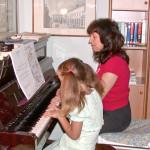 Piccola alunna suona un brano a quattro mani con l'insegnante